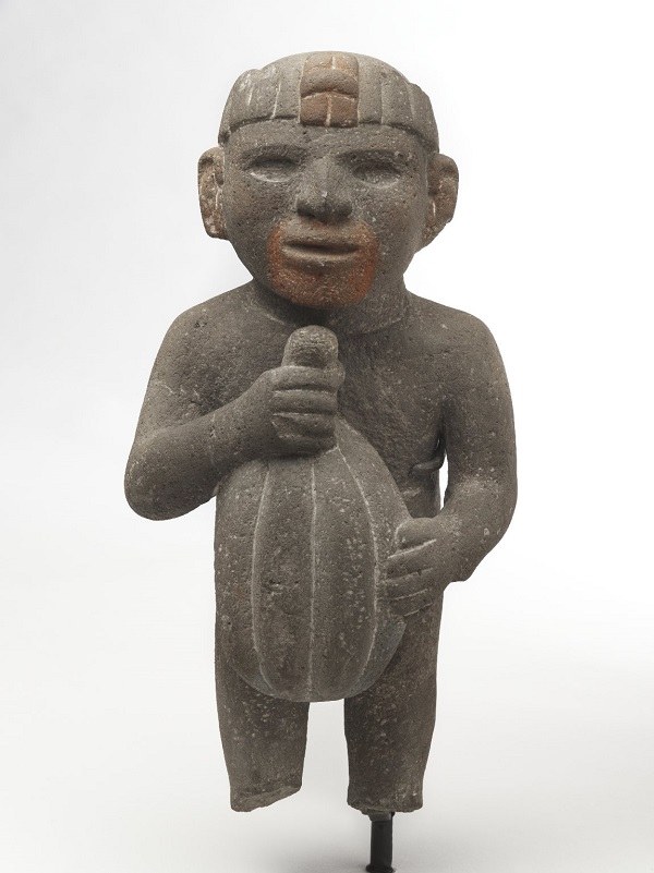 Statue of an Aztec man with a neutral expression on his face. He carries a huge cacao pod in his arms. Over the years, his feet have broken off.