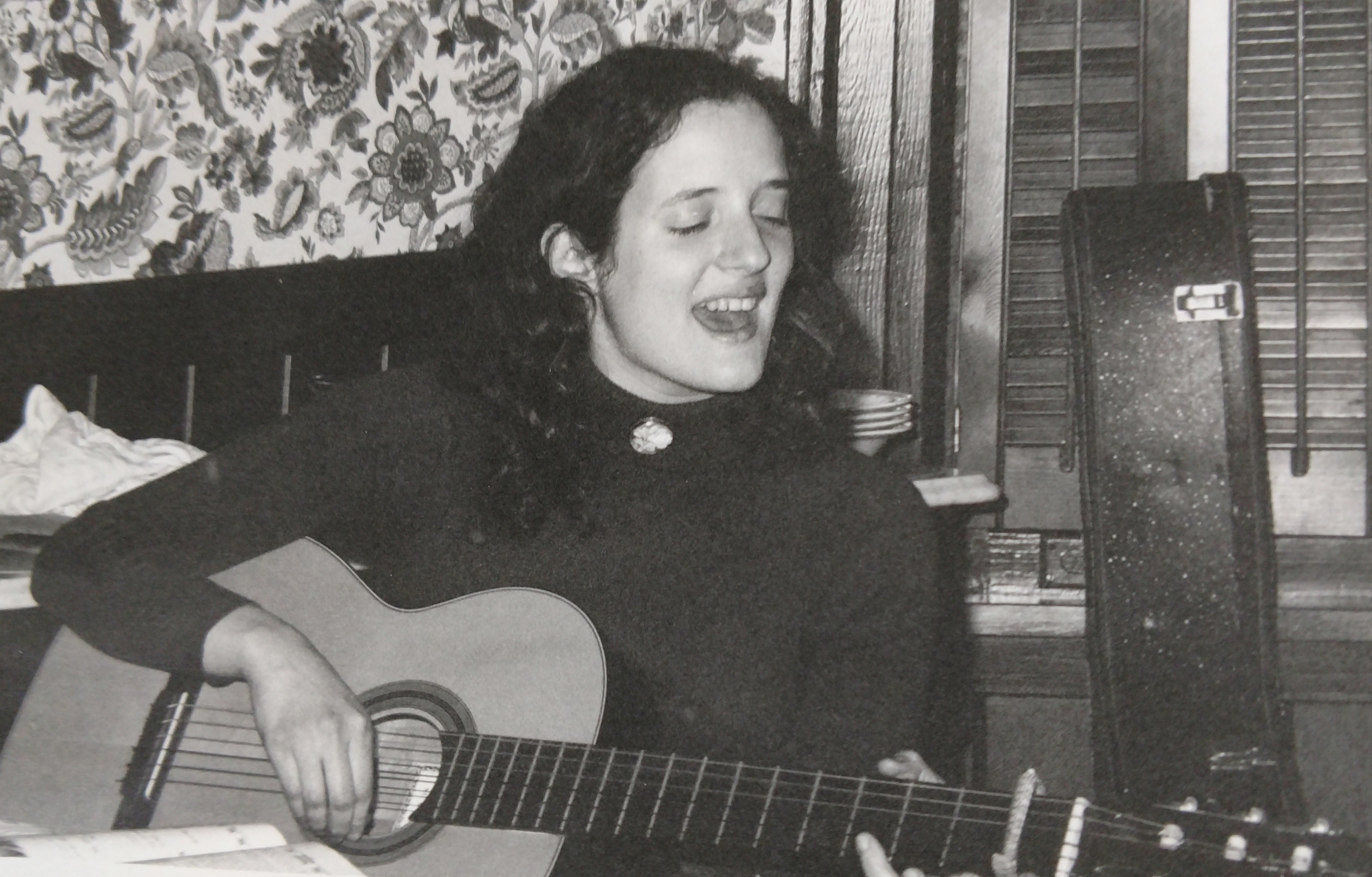 A vintage picture of a woman singing and strumming an acoustic guitar