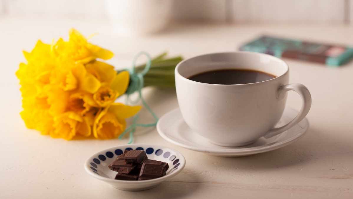 A cup of organic coffee on a table with organic chocolate and some daffodils