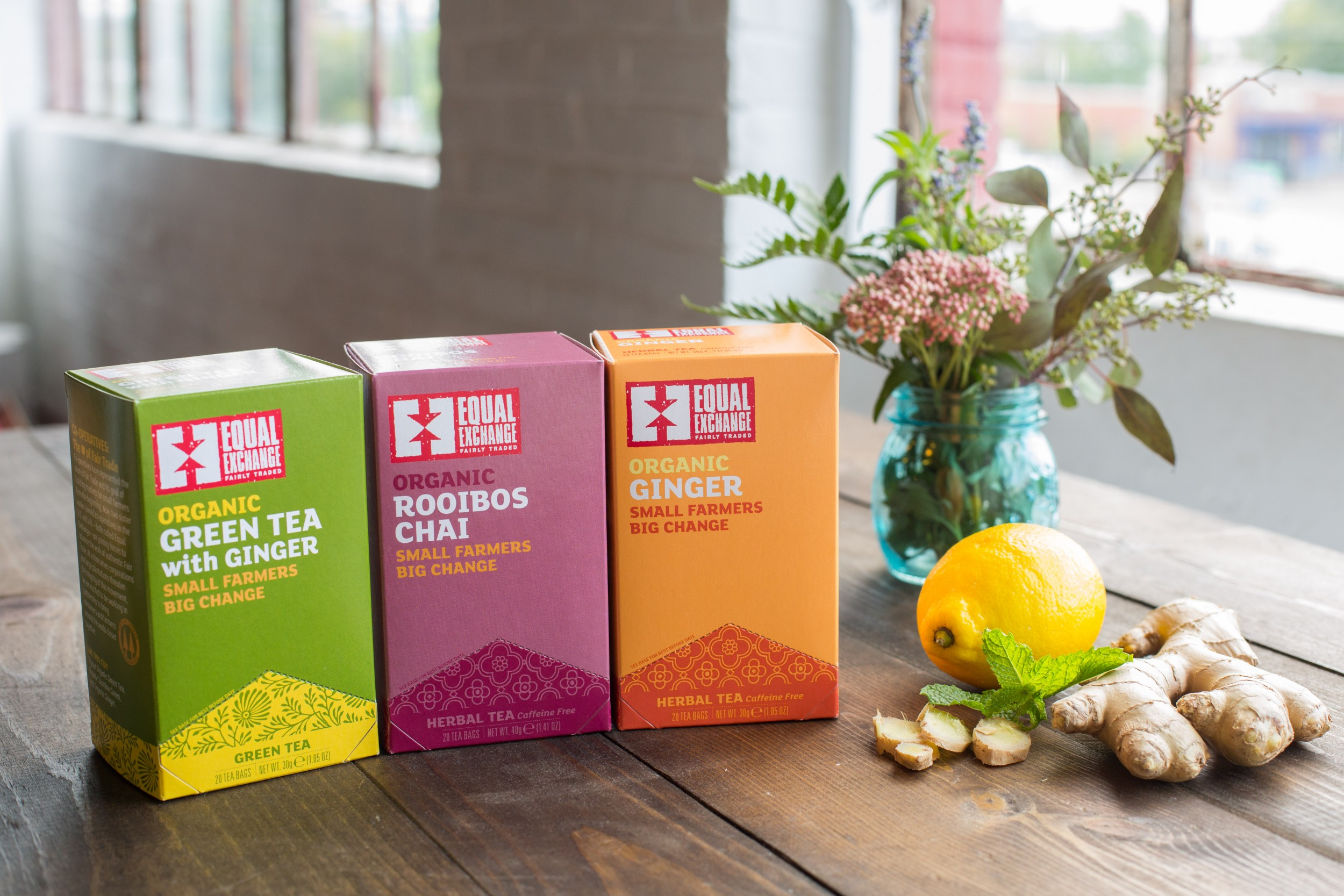 Image shows three boxes of Equal Exchange's organic, fairly traded teas on a table top with a vase of spring flowersrs