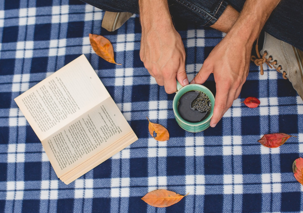 An open book and a person's hands holding acup of fair trade coffee