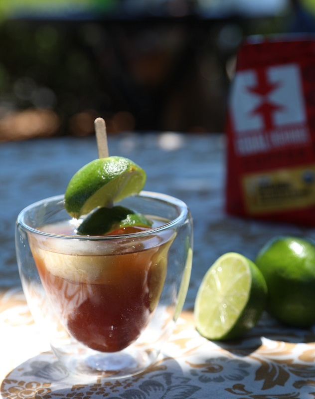 A cold brew lime daiquiri in a glass with ice sits in the sun next to two limes and a bag of organic coffee.