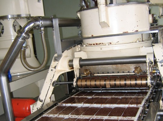 Finished chocolate bars roll out of a machine in their molds