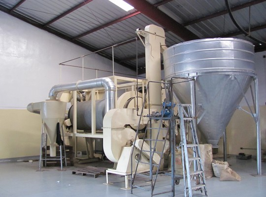 A stainless steel funnel and a machine with a lot of tubes in a chocolate processing facility
