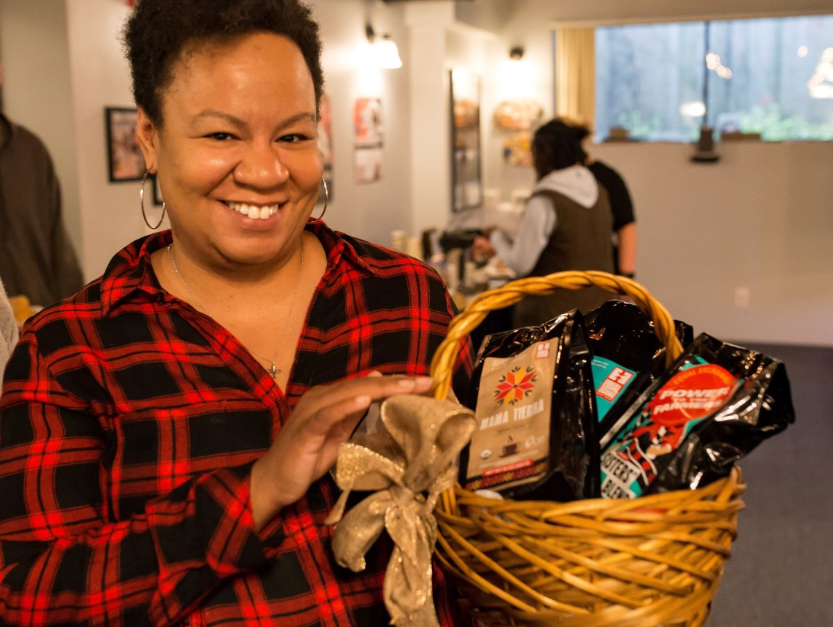 A woman holds a gift basket full of fair trade coffee