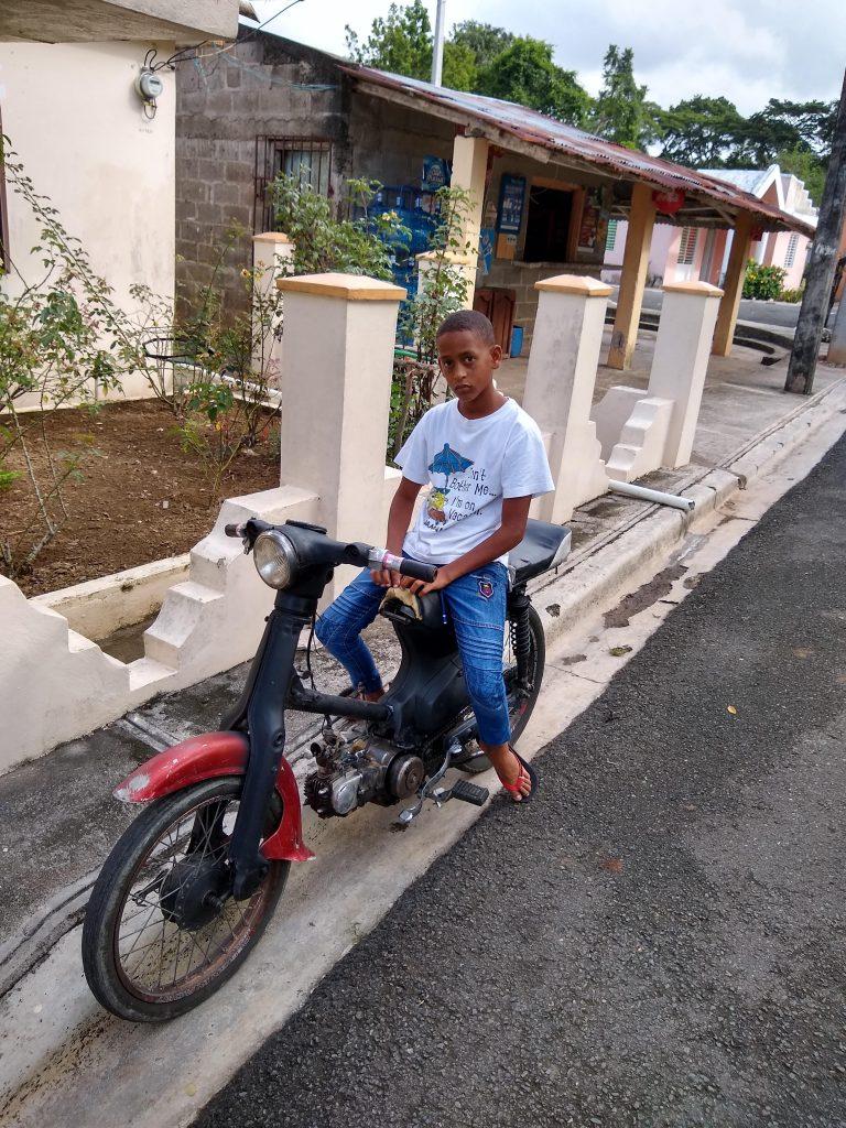 A boy stands astride a motorbike.