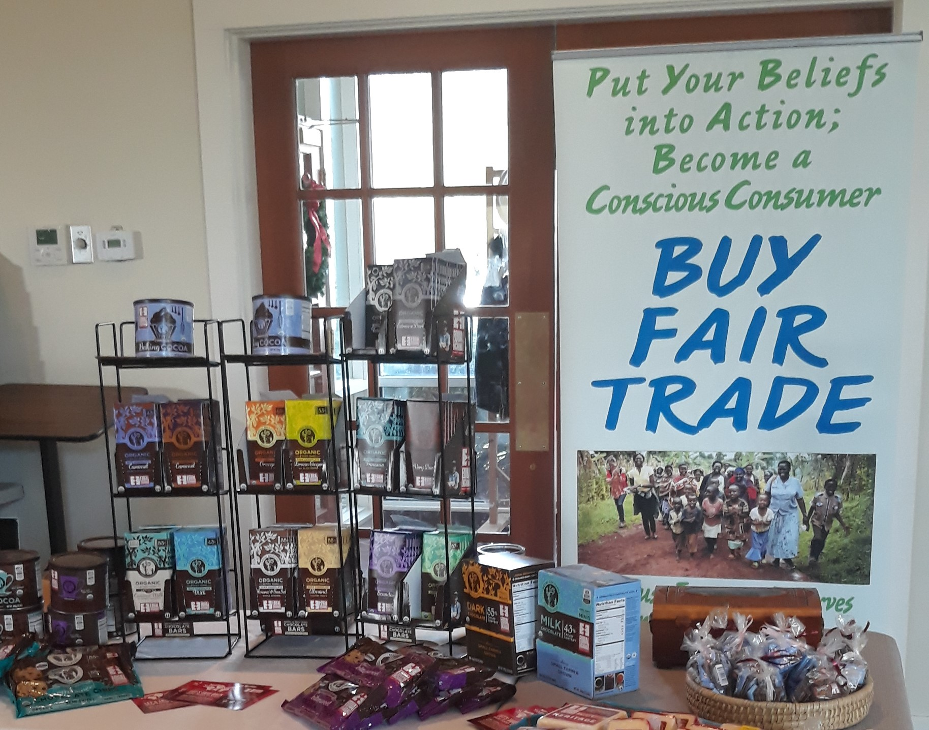 "A sale table full of Equal Exchange chocolates and a sign that says ""Buy Fair Trade: Put your Beliefs into Action;Become a Conscious Consumer"""