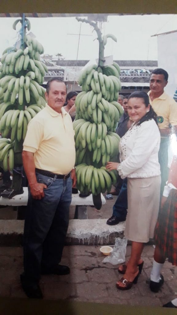 Cecilia and her father present bananas grown on their farm